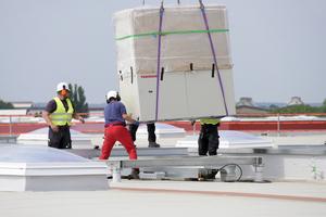 Die auf dem Dach montierten Yanmar-Gasmotorwärmepumpen wiegen jeweils 1.080 kg und werden von vier Monteuren entgegengenommen.