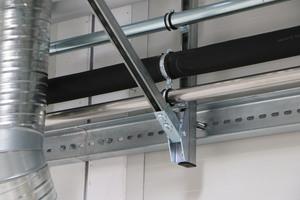 """Befestigungsdetail des Universal-Schienensystems """"FUS"""" mit Rohrschellen zur Sicherung der Heizungs- und Kälteleitungen in der Produktionshalle."""