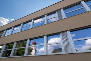 Der Klassentrakt wurde umfassend modernisiert. Parallel zu den neuen Fenstern wurden auch die Lüftungsgeräte installiert, deren Wetterschutzgitter sich in das Fensterband einfügen.