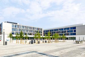 """Der neue Schulkomplex besteht aus zwei L-förmigen Hauptgebäuden, in denen die beiden Schulen untergebracht sind, einem diese Gebäudeteile verbindenden """"Flurcampus"""" sowie einer Zwei- und einer Vier-Feld-Sporthalle."""