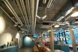 """Alle öffentlichen Räume im Erdgeschoss werden von der Sichtinstallation geprägt, so auch der Frühstücksraum. Die Sanha-Systeme """"NiroSan"""" für Trinkwasser und """"NiroTherm"""" für Heizung und Kälte sind gedämmt."""