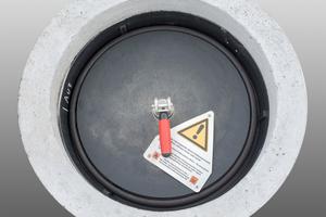 Einstiegsöffnung von oben: Zweite Dichtebene mit PE-Deckel und Hinweis zur Sicherheit in Bezug auf CO-Messung beim Einstieg.