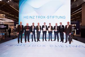 Auf der Trox-ISH-Bühne: Die beiden Preisträger Erik Alves und Lucas Schiffhauer (Mitte), umrahmt von ihren Professoren, den Verantwortlichen der Heinz Trox-Stiftung sowie Mitgliedern der Auswahljury.