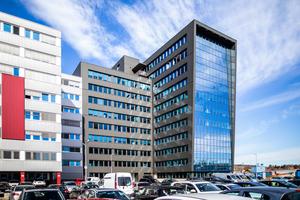 Der zehngeschossige Neubau (hier: Süd-West-Ansicht) grenzt an ein Bestandsgebäude, mit dem die Fassade in Glas und Anthrazit optisch sehr gut harmoniert.