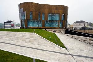 Hinter der außergewöhnlichen Fassade verbergen sich auf vier Etagen ein bekanntes Mode-Label und der Verwaltungskomplex. Die Geschäftsbrücke verbindet dabei das Areal Döppersberg mit der nahegelegenen Fußgängerzone. Bei der Planung des Areals kam die BIM-Methode zum Einsatz.
