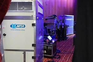 Blick auf die Konferenztechnik und Lüftungsgeräte hinter der Veranstaltungsbühne