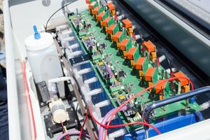 Der Demonstrator des Speichers soll seinen Aufbau verdeutlichen. Die blauen Kästen sind die Zellen, im Gefäß links befindet sich das Elektrolyt, das durch die Schläuche weitergeleitet wird.