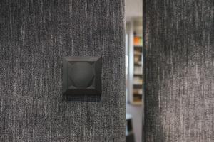 Betätigt ein Mitarbeiter den Touch Taster, öffnet sich ein in sonst der Wand versteckter Zugang zum Drucker.