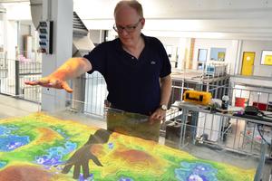 """Prof. Dr. Helmut Grüning lässt es virtuell regnen. Die """"Augmented Reality Sand Box"""" gehört zum neuesten Lehr-Equipment des Technikums für Hydraulik und Stadthydrologie."""