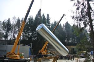 Aufstellung des Pufferspeichers. Zwei Kräne bringen den 16 m hohen und 12 t schweren Behälter in Position. Viel Platz für Wärme auf Vorrat: Sein Speichervolumen liegt bei 100 m<sup>3</sup>.
