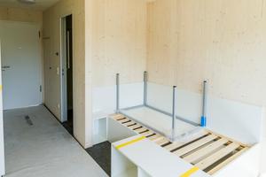 Die 18 m² großen Studentenappartements wurden voll ausgestattet auf der Baustelle angeliefert. Die sichtbaren Holzinnenwände sind im Brandschutzkonzept durch Brandschutzmaßnahmen an den Außenwänden der Module kompensiert.