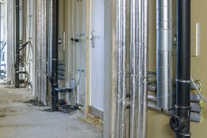 In den Fluren werden Trockenbauwände (F60) eingezogen und bilden damit die Steigeschächte. Eine spezielle Brandschutzabschottung der Leitungsdurchführung der Holzmodule ist deshalb nicht erforderlich.