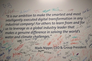 """Vision von Mads Nipper, gesehen im """"Digital Transformation Office"""" in Bjerringbro. Mitarbeiter von Grundfos haben das per Unterschrift gegengezeichnet.""""Unser Ziel ist die cleverste und am intelligentesten umgesetzte digitale Transformation eines Industrieunternehmens. Und das so, dass Andere davon lernen können – und wir uns als globaler Marktführer profilieren, der entscheidend zur Lösung der weltweiten Wasser- und Klimaherausforderungen beiträgt."""""""