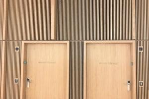 Die Flurwände der Hörsäle im 1. OG und 2. OG sind mit Lamellen aus Eichenholz ausgeführt. In die vertikale Struktur sind auch die Öffnungen der Indusilent Überströmelemente eingebunden.