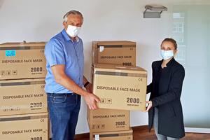 Sinah Gickeleiter, Leiterin der Geschäftsstelle des ITGA BW, übergibt die ersten Schutzmasken an Steffen Hild, Geschäftsführer der Clean Air Technology GmbH.