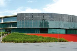 """Bei der EWE-Arena in Oldenburg """"umkreist"""" ein Wandschirm mit integrierten PV-Modulen die Glasfassade."""