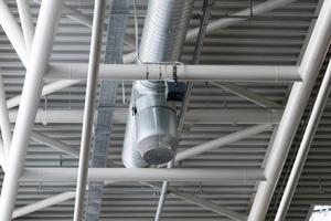 Luftauslass unter der Hallendecke in der luftigen Höhe von etwa 15 m. Wärme wird ausschließlich über die Zentrallüftungsanlagen abgeführt.