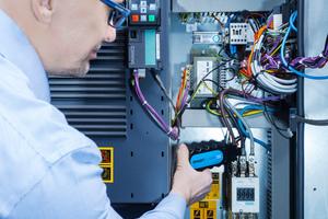 """Andreas Theis führt die Funktionsweise der """"Smart Clamp"""" vor. Damit funktioniert """"Smartlink"""" auch bei kleineren Kompressoren, die keine """"Elektronikon""""-Steuerung haben."""