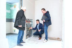 Paul Bartenstein (Mitte), Technischer Fachberater bei KaMo/Uponor, zeigt den Fachplanern Harald Kirchner (links) und Michael Kirchner (rechts) die Vorteile der KaMo-Wohnungsstation.