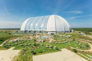 """Der Dome von Tropical Islands mit dem Außenbereich """"Amazonia"""". Der Kuppelbau zählt zu den größten freitagenden Hallen der Welt und war ursprünglich zur Unterbringung von Zeppelinen konzipiert worden."""