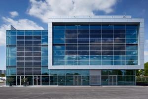 Das Event- und Konferenzgebäude Brand Experience Center der Audi AG am Flughafen München verfügt über 1.650 Photovoltaik-Elemente (dunkle Glasflächen), deren Strom für die Versorgung des Gebäudes und der Ladestationen für E-Fahrzeuge genutzt wird.