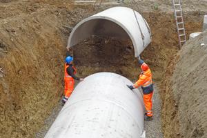 Das letzte der vier Tunnelteile kann direkt vom Kran des Lieferfahrzeugs aus eingepasst werden. Vom Filterschacht wird anschließend die Zulaufleitung an die Rückwand des letzten Segments angeschlossen.