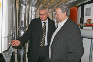 Josef Holmer, SportSchloss Velen, (rechts) und Frank Draber, Remeha, begutachten die Installation der Zweierkaskade; im Hintergrund zwei Speicher, die von der Höhe her gerade noch in den Kellerraum eingebracht werden konnten