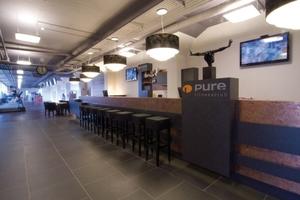 """Lounge, Sport, Sauna &amp; Spa – das """"Pure"""" ist alles in einem; die attraktive Café-Bar im Eingangsbereich ist zugleich zentraler Mittelpunkt und verbindet den Gerätesport- mit dem Gymnastik- und Wellnessbereich.<br />"""
