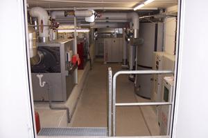Blick in den Heizraum: Die Heizzentrale besteht aus Niedertemperatur-Gaskessel und BHKW (links), Schaltschränken DDC/BHKW sowie Pufferspeicher und Wärmepumpe (rechts)<br />