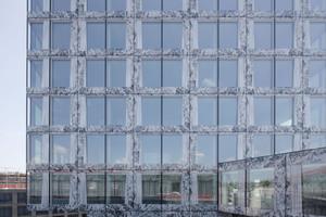 Der Hohlraum in der Fassade veerfügt über einen mechanischen Sonnenschutz in Form eines aluminiumbedampften Textilvorhangs