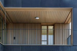 Detail einer in das Gebäudevolumen eingeschobene Loggia - mit Holz ausgekleidet sorgen diese für eine wohnliche Atmosphäre.