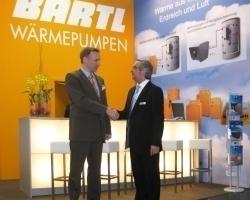 Jürgen Lang, Geschäftsführer von Bartl Wärmepumpen und Michael Sautter, Geschäftsführer der perma-trade Wassertechnik GmbH, besiegeln ihre Zusammenarbeit im Bereich Heizungswasseraufbereitung per Handschlag auf der Fachmesse IFH/Intherm in Nürnberg