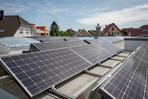 Heinz Jörg Göbert auf dem Flachdach seines Bungalows inmitten von 69 Photovoltaikmodulen