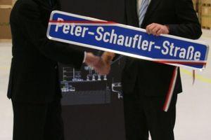 Der Oberbürgermeister der Stadt Rottenburg am Neckar, Stephan Neher, übergibt das Straßenschild an Peter Schaufler