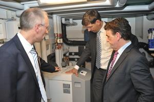 Andreas Klapdor und Dr. Norbert Verweyen (beide RWE) mit dem Minister für Bauen und Wohnen in NRW, Michael Groschek (von links) im Technikraum des Effizienzhauses an der Stiebel Eltron-Wärmepumpe
