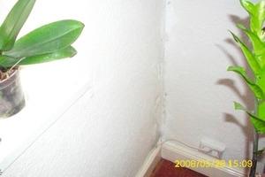 Feuchteschaden im Eckbereich einer Außen- und Innenwand in einem Wohnzimmer. Ursache für die dunkle Verfärbung der Tapete ist eine Wärmebrücke im Eckbereich, an der sich die nicht abgeführte Raumluftfeuchte niederschlägt; zur Vermeidung von Feuchteschäden ist in diesem Fall eine Wohnraumlüftung nachzurüsten<br />