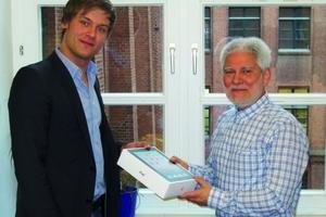 Walter Meier-Mitarbeiter Marc Pöhlitz übergibt in Berlin ein Apple iPad an den Gewinner der Verlosung beim Klima Forum 2011, Herrn Gielich vom Ingenieurbüro P2B.