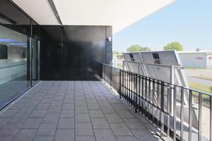 Am Geländer der Obergeschoss-Loggia wurden zu Übungszwecken zwei Photovoltaikelemente installiert. Eine rd. 4.000m² große PV-Anlage befindet sich auf dem Dach des benachbarten Hauptgebäudes.