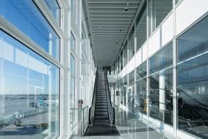 Blick auf die Klimafassade: Im Zwischenraum befinden sich die Rolltreppen, mit denen die Fluggäste zwischen den drei Passagierebenen wechseln können. Der gesamte Umsteige- und Bewegungsverkehr der Passagiere wird über die Klimafassade auf einer Ebene geregelt, so dass man nur eingeschossige Fluggastbrücken benötigt.