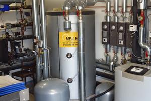 Blick in die Heizzentrale im Erdgeschoss: In der Mitte der Wärmespeicher für das durch die Wärmepumpe (rechts) erhitzte Wasser. Mit deren Hilfe wird die durch Solarthermie (Sonneneinstrahlung auf die Bioreaktoren) gewonnene Wärme auf den in der Heizung erforderlichen Wert von 30°C gebracht.