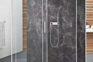 """Das Koralle-Wandsystem """"WS60"""" bietet neue Dimensionen der individuellen Badgestaltung und harmoniert mit den Duschwannen und -abtrennungen des Herstellers. Hier bildet die Natursteinoptik """"Patina Rock"""" die Rückwand der Duschabtrennung """"S606Plus""""."""