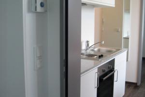 Blick in den Küchenbereich einer Wohnung, vorne die Fernbedienung mit Gegensprechanlage, Fenstersteuerung und Schalter<br />