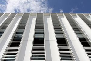 Die Fassade aus vertikalen Lisenen und horizontalen Lamellen minimiert den Reflexionsanteil (Stealth-Technik); dadurch ist ein störungsfreier Radarbetrieb am Flughafen gewährleistet