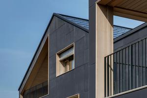 Fassadendetail mit eingeschobenen Loggien und Fensteröffnungen – die gesamte Gebäudehaut liefert Solarstrom und sorgt mit den in Holz ausgekleideten Loggien und Fensterleibungen für eine elegante Architektursprache.