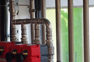 Blick aus dem Technikraum im Erdgeschoss durch die Fassade mit Bioreaktoren nach außen. Links im Bild Ventile (rot) zur Steuerung der Versorgung der Mineralstoffzufuhr für die Algen.